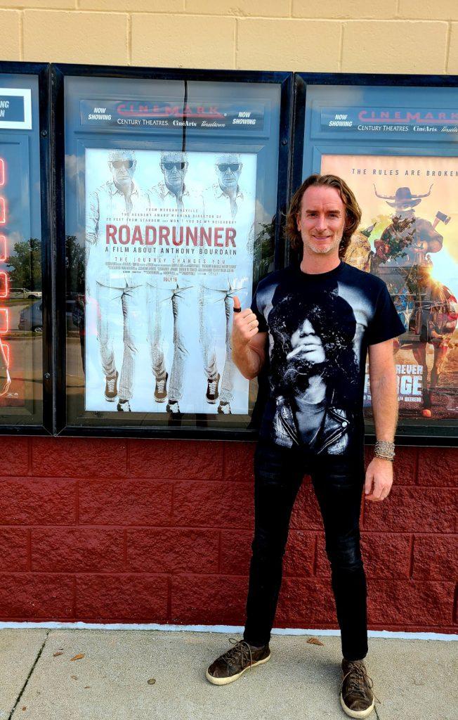 Standing in front of Roadrunner Anthony Bourdain film movie poster